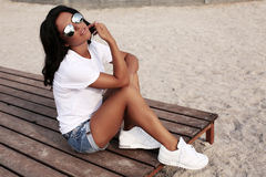 Beautiful tanned girl with dark hair in casual clothes. Fashion outdoor photo of beautiful tanned girl with dark hair in casual clothes and sunglasses relaxing Stock Photography