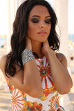 Beautiful tanned girl with dark hair in elegant dress with accessory Royalty Free Stock Photo