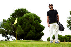 Beautiful tanned guy on the golf course. Full length portrait of stylish golfer man in glasses standing on beautiful golf course looking away, handsome brunette stock photo