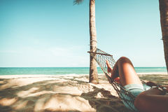 Beautiful Tanned legs of sexy women. relax on hammock at sandy tropical beach. Royalty Free Stock Image