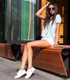 Beautiful tanned long-legged girl in white shorts, green T-shirt, white sneakers and fashion sunglasses resting on a bench in an o Royalty Free Stock Photos