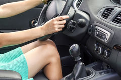 Beautiful tanned slim woman driver legs in a car. Girl in dress. Driving a car Stock Photography