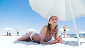 Beautiful tanned smiling woman is lying on the beach on a white sand, relaxing and listen music from the phone with. Beautiful tanned happy laughing woman is stock footage