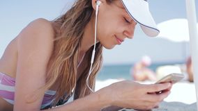 Beautiful tanned smiling woman is lying on the beach on a white sand, relaxing and listen music from the phone with. Beautiful tanned happy laughing woman is stock video footage