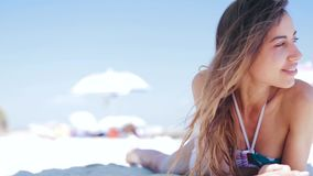 Beautiful tanned smiling woman is lying on the beach on a white sand, relaxing and listen music from the phone with. Small headphones. Slim sexy woman in bikini stock footage