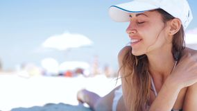 Beautiful tanned smiling woman is lying on the beach on a white sand, relaxing and listen music from the phone with. Small headphones. Slim sexy woman in bikini stock video footage