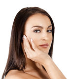 Beautiful tanned woman. Beautiful tanned Italian woman touching her face applying cream and smiling over white background Royalty Free Stock Image
