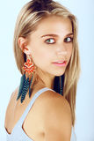 Beautiful tanned woman. Beautiful tanned young woman with blond hair wearing a summer dress and coral and blue feather earrings on studio background Royalty Free Stock Photos