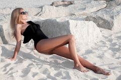 Beautiful tanned woman in black swimsuit on the beach. Stock Photo