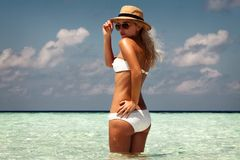 Beautiful tanned woman on maldives island beach with turquoise s stock photography