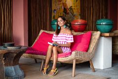 Beautiful tanned woman sits on a pink sofa with a book in her hands. Posing and smiling royalty free stock photography