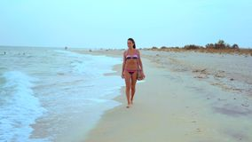 Beautiful Tanned Woman in Striped Swimsuit Walking along the Sea Shore. Beautiful Tanned Woman in Striped Swimsuit and Shoulder Bag Walking along the Sea Shore stock footage
