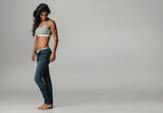 Beautiful tanned woman with unbuttoned jeans Royalty Free Stock Photography