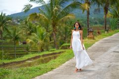 Beautiful tanned woman in white dress posing standing on the road. In the background are palm trees and other tropical vegetation royalty free stock photography