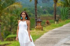 Beautiful tanned woman in white dress posing standing on the road. In the background are palm trees and other tropical vegetation. Close up stock image