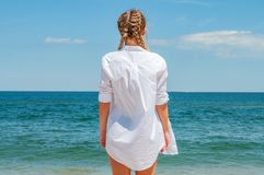 Beautiful tanned woman in white shirt looking at ocean, on the beach. Enjoying freedom royalty free stock images