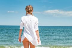 Beautiful tanned woman in white shirt looking at ocean, on the beach. Enjoying freedom stock image