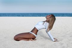 Beautiful tanned woman in a white swimsuit on the beach. Royalty Free Stock Images