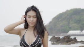 Beautiful tanned young asian woman in bikini playful at the beach.