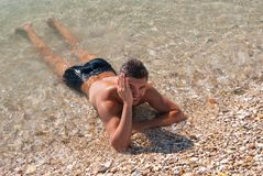 Beautiful tanned young fellow in sea water Stock Image
