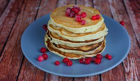 Beautiful tasty punkcakes with red currant berries. Beautiful tasty punkcakes with strawberry sauce and red currant berries on a blue plate on a wooden Royalty Free Stock Photo