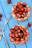 Beautiful tasty tarts with fresh strawberries, mascarpone and li. Corice syrup on bright blue table overhead view royalty free stock photography