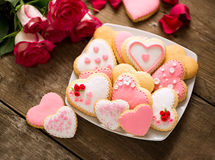 Beautiful tasty valentine day cookies on plate and roses Stock Photography