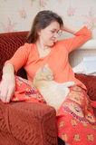 Beautiful tatar woman on the chair relaxing with cat and reading magaz Stock Photo