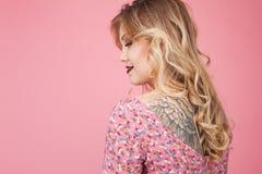 Beautiful tatooed woman wearing pink dress Stock Photo