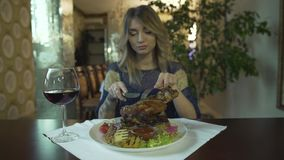 Beautiful tattooed blonde girl young woman waiting to eat huge piece of fried meat with hands in fancy restaurant stock footage
