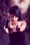 Beautiful tattooed girl with attitude holding gun Royalty Free Stock Photography