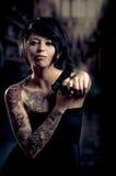 Beautiful tattooed girl with attitude holding guns Stock Photo