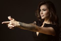Beautiful tattooed woman with luxuriant shining wavy hair and perfect make up pretending to aim something with shooting gesture. Portrait of young beautiful stock photo