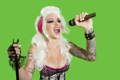 Beautiful tattooed woman singing with microphone over green background Royalty Free Stock Images