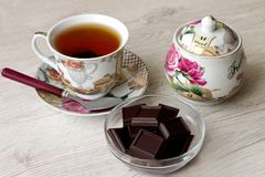 Beautiful tea set with chocolate stands on a wooden surface royalty free stock photos