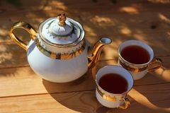 Beautiful tea set, porcelain teapot. With beautiful pattern, gilt, and two cups with black tea, on wooden table, summer get-togethers on Fazenda royalty free stock photography