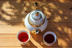 Beautiful tea set, porcelain teapot. With beautiful pattern, gilt, and two cups with black tea, on wooden table, summer get-togethers on Fazenda royalty free stock photo