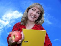 Beautiful teacher. Holding an apple on sky background Stock Photo