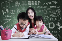 Beautiful teacher help children to write in class Stock Photography