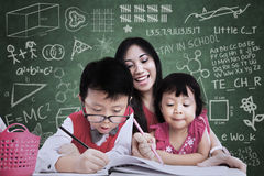 Beautiful teacher see children writing in class Stock Photography