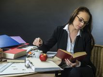 Beautiful teacher sitting at her desk reading. Photo of a teacher or business woman in her 30`s sitting at a desk in front of a large blackboard reading royalty free stock image