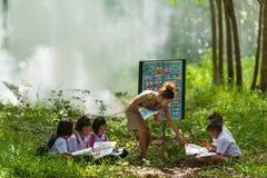 Beautiful teacher in uniform teaching her students outdoor class Stock Image