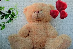 Beautiful teddy bear sitting on a light background holding hearts royalty free stock images