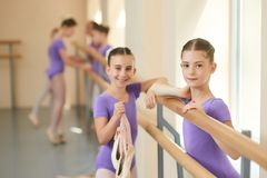 Beautiful teen ballerina leaning on barre. Cute young girls dancers in purple leotard at ballet dance hall Stock Image