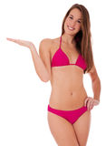 Beautiful teen in bikini pointing to the side Royalty Free Stock Images