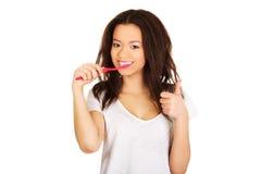 Beautiful teen brushing her teeth. Stock Photo