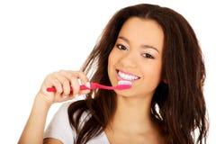 Beautiful teen brushing her teeth. Stock Image