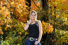 Beautiful teen country girl among fall foliage. Beautiful young teen girl in black tanktop and jeans in front of fall foliage yellow smiling royalty free stock images