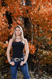 Beautiful teen country girl among fall foliage. Beautiful young teen girl in black tanktop and jeans in front of fall foliage stock photos