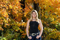 Beautiful teen country girl among fall foliage. Beautiful young teen girl in black tanktop and jeans in front of fall foliage royalty free stock images